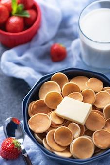 Gros plan de petites crêpes aux céréales avec tranche de beurre, fraises, verre de lait sur bleu