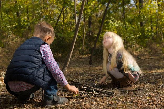 Gros plan sur les petits enfants blancs en tenue d'automne jouant dans la forêt avec des arbres en arrière-plan.