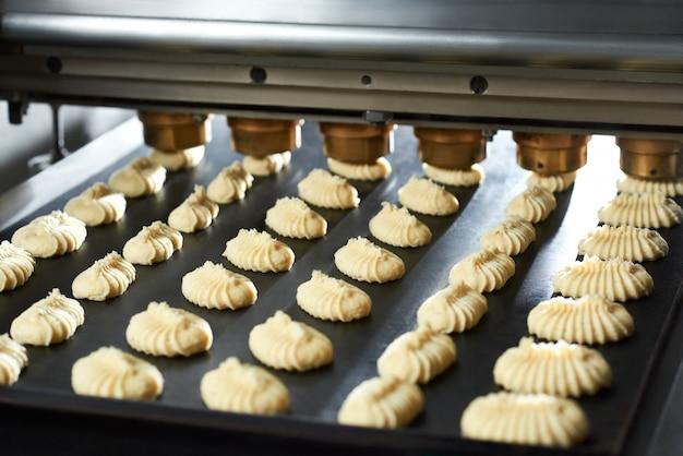 Gros plan de petits gâteaux de pâte crue dans le plat arrière sur la ligne de boulangerie.