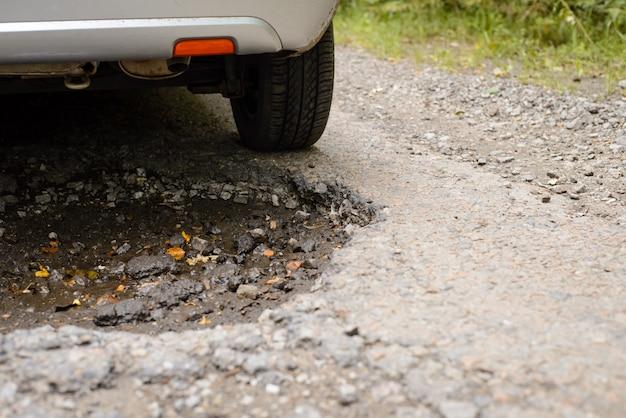 Gros plan photo de l'arrière de la voiture roulant à travers un énorme nid de poule profond dans la route goudronnée
