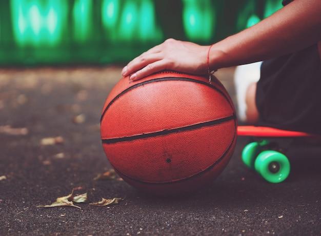Gros plan photo ballon de basket avec une fille assise sur un shortboard en plastique orange penny sur l'asphalte