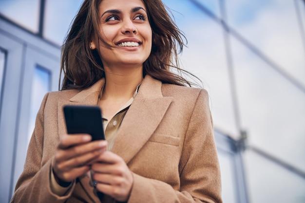 Gros plan photo d'une belle jeune femme avec un téléphone portable dans les mains, debout près d'un bâtiment en verre