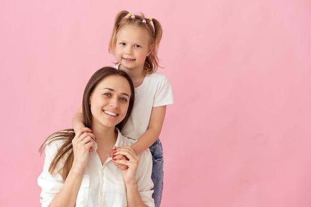 Gros plan photo d'une belle jeune mère étreignant sa petite fille. meilleurs amis câlins, sentiments cardiaques sincères isolés sur fond de couleur rose pastel.