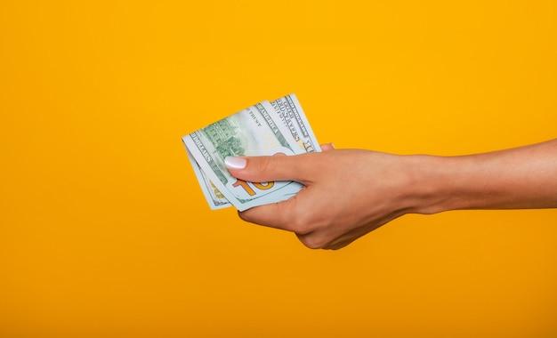 Gros plan photo de belles mains féminines tenant le tas de dollars des états-unis isolé sur fond jaune. concept économique, commercial et financier