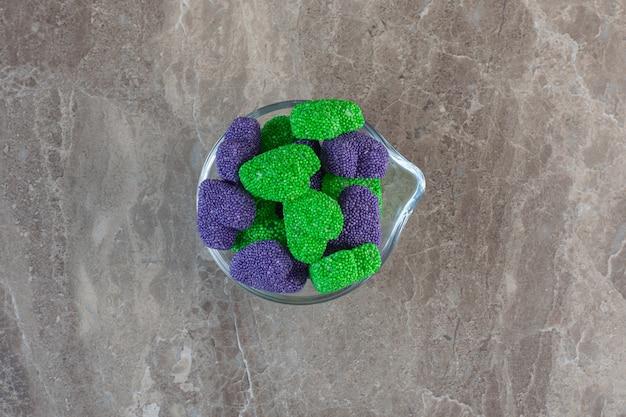 Gros plan photo de bonbons colorés en forme de coeur dans un bol en verre.