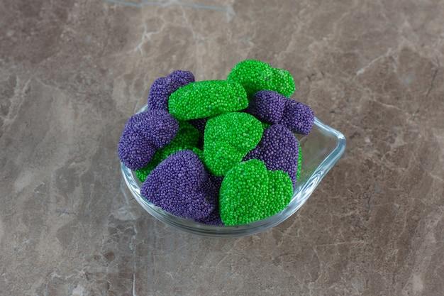 Gros plan photo de bonbons sucrés verts et violets en forme de coeur.
