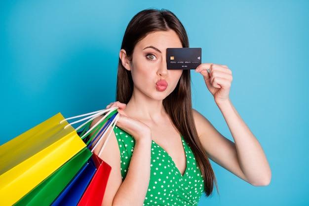 Gros plan photo charmante fille centre commercial client fermer les yeux de couverture carte de crédit faire des lèvres boudeuses dodues tenir des sacs porter des débardeurs verts pointillés débardeur isolé fond de couleur bleu
