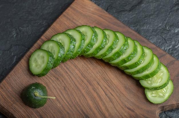 Gros plan photo de concombre frais tranché sur planche de bois. photo de haute qualité