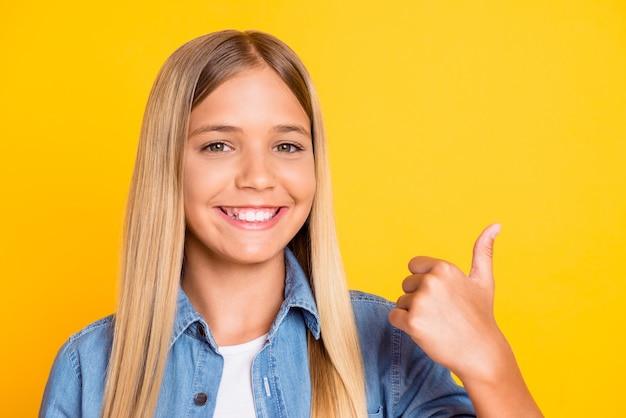 Gros plan photo d'une écolière blonde heureuse et amicale montrant le pouce vers le haut souriant portant une chemise en jean isolée sur fond de couleur jaune vif