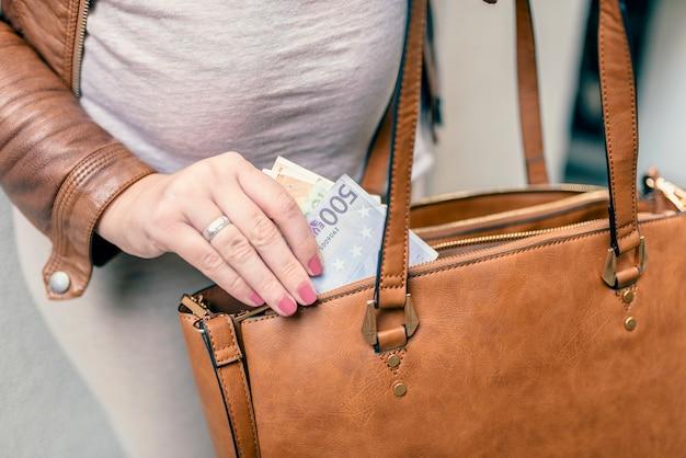 Gros plan photo de femme élégante, prendre l'argent sur le sac. femme se prépare à payer