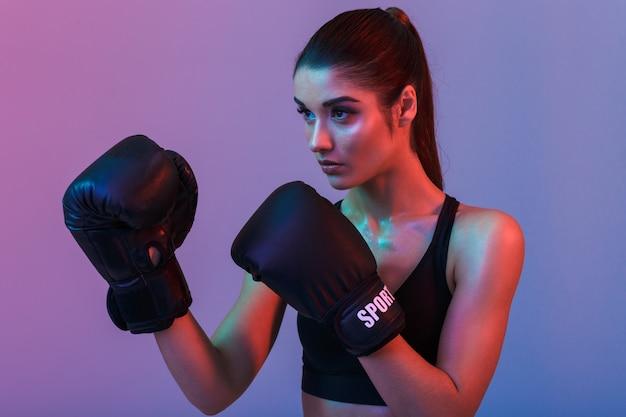 Gros plan photo de femme forte concentrée 20 ans en boxe soutien-gorge sportive dans des gants noirs pendant la formation en salle de sport, isolé sur mur violet