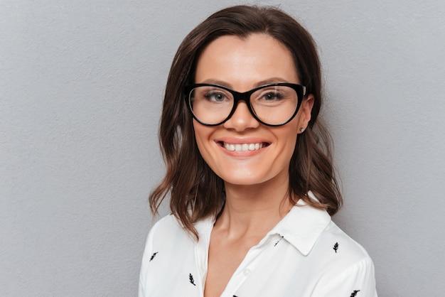 Gros plan photo de femme heureuse à lunettes en regardant la caméra sur gris