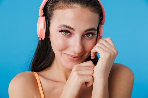 Gros plan photo d'une femme joyeuse séduisante à l'aide d'écouteurs et souriant