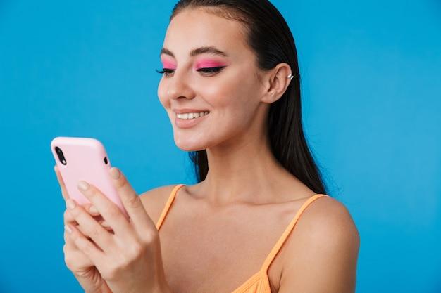 Gros plan photo d'une femme joyeuse séduisante utilisant un téléphone portable et souriant