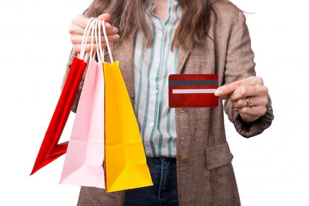 Gros plan photo de femme montrant une carte de crédit et des sacs à provisions.