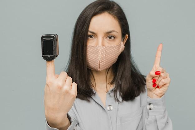Gros plan photo femme avec oxymètre de pouls sur son doigt, vérifie sa santé