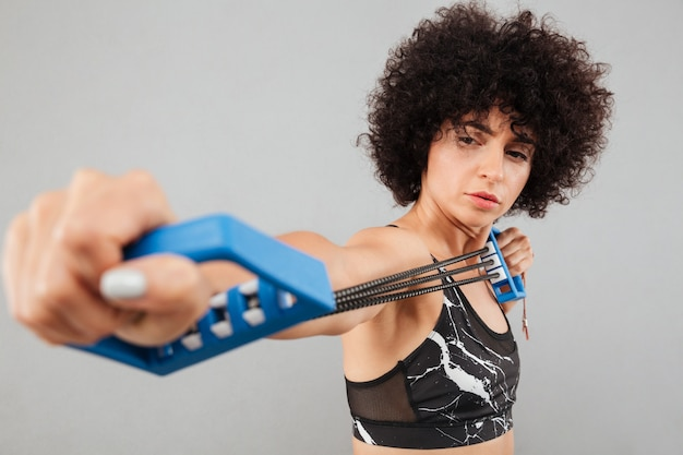 Gros plan photo de femme sportive bouclée concentrée, faire de l'exercice