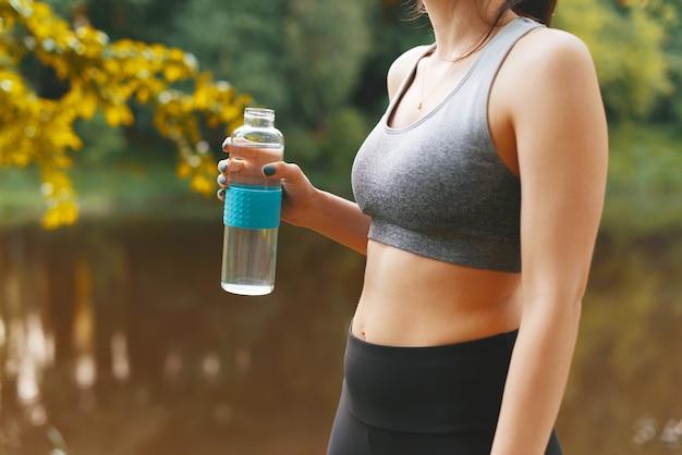 Gros plan photo d'une femme sportive à l'extérieur au coucher du soleil tenant une bouteille d'eau en verre, restez hydraté