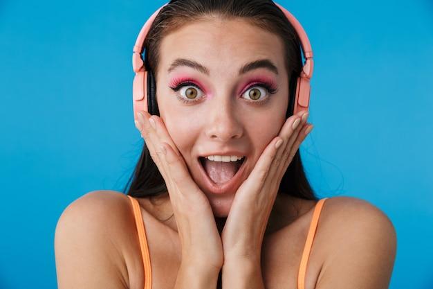 Gros plan photo d'une femme surprise séduisante à l'aide d'écouteurs
