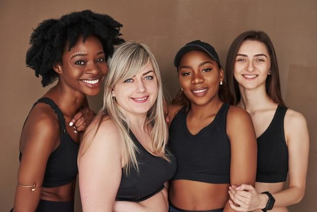 Gros plan photo. groupe de femmes multiethniques debout contre l'espace brun