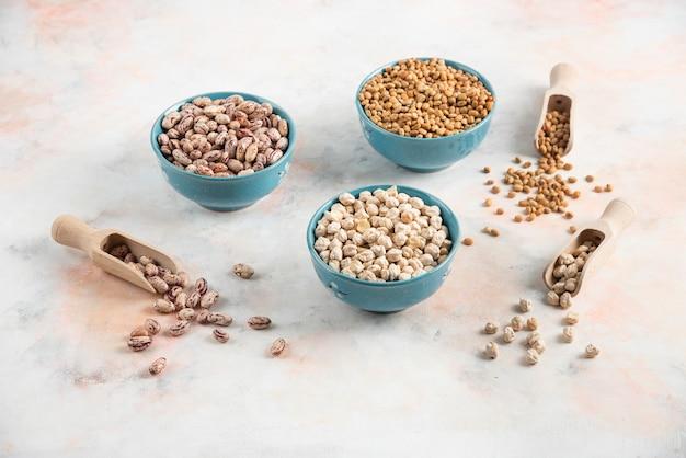 Gros plan photo de haricots, pâtes et pois chiches dans des bols sur une surface blanche.