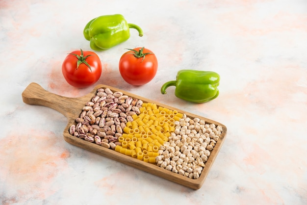 Gros plan photo de haricots, pâtes et pois chiches sur un plateau en bois avec des légumes frais.
