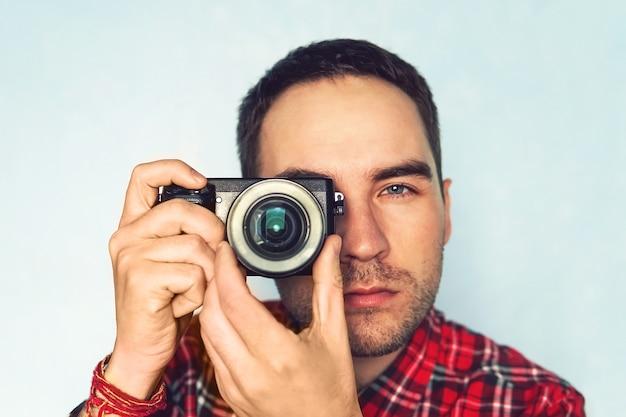 Gros plan photo d'un homme au chapeau sur fond bleu prenant une photo avec un appareil photo numérique sans miroir. jeune reporter photo masculin mignon avec un petit appareil photo dans ses mains. des paparazzis habillés de manière décontractée prennent des photos.