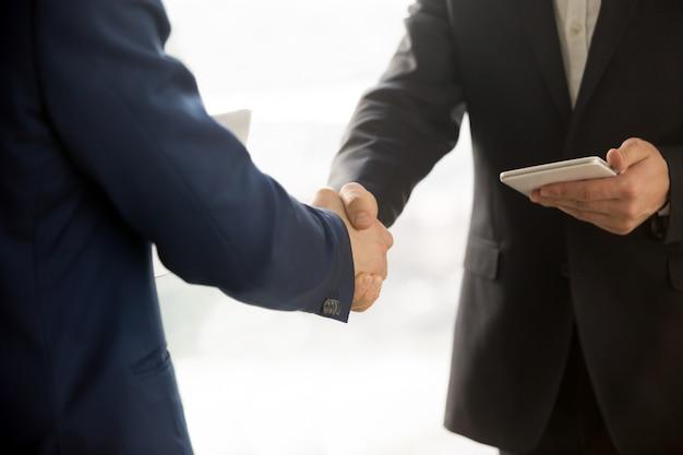 Gros plan photo d'hommes d'affaires informatiques se serrant la main
