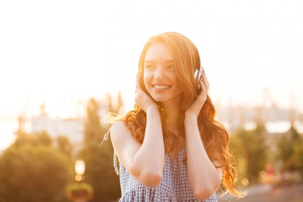 Gros plan photo de jeune beauté femme au gingembre en robe écouter de la musique sur le coucher du soleil