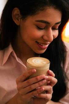 Gros plan photo d'une jeune femme aux cheveux noirs regardant vers le bas et souriant tout en ayant un verre de latte dans ses mains
