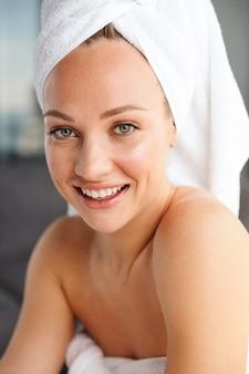 Gros plan photo de jeune femme joyeuse enveloppée dans des serviettes blanches à la recherche et souriant