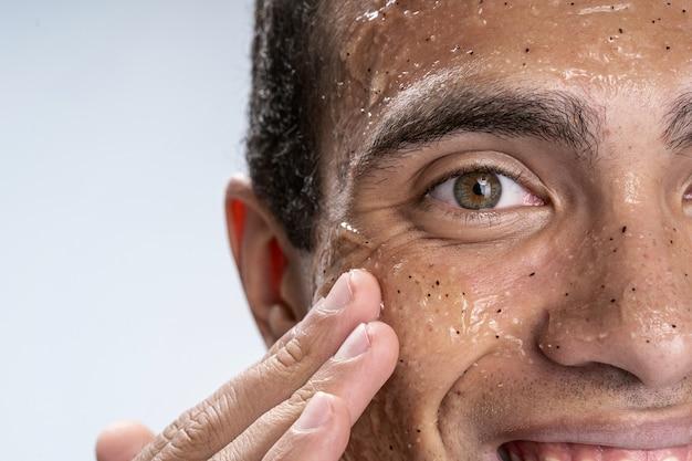 Gros plan photo d'un jeune homme avec un masque facial d'humidité