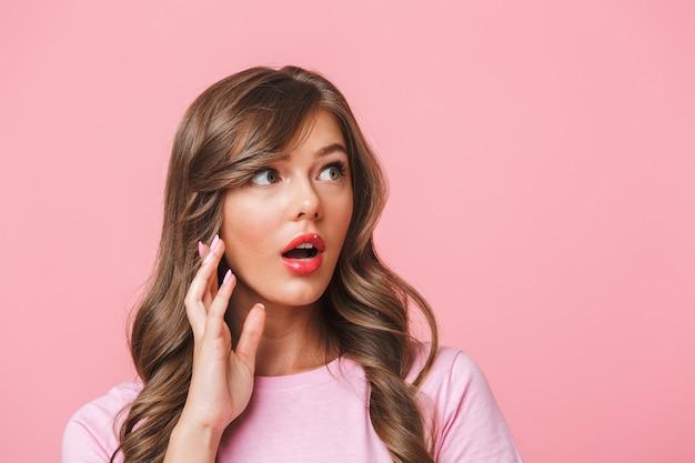Gros plan photo de jolie femme excitée avec de longs cheveux bouclés en t-shirt de base les yeux exorbités et regardant de côté avec surprise et bouche ouverte, isolé sur fond rose