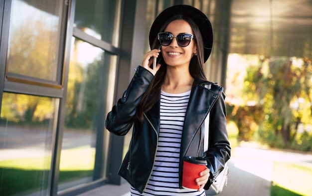 Gros plan photo d'une jolie femme en veste de cuir et lunettes de soleil, qui sourit largement tout en tenant un smartphone dans sa main droite et une tasse de café dans sa main gauche