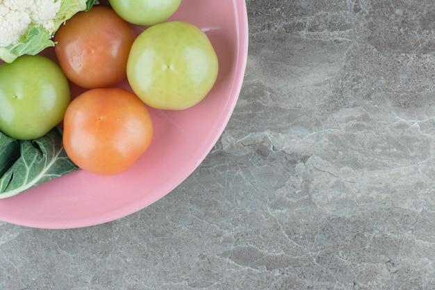 Gros plan photo de légumes biologiques frais sur plaque rose.