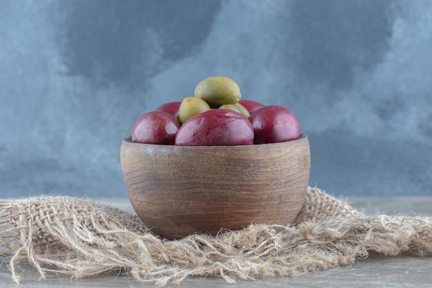Gros plan photo de légumes en conserve dans un bol en bois.