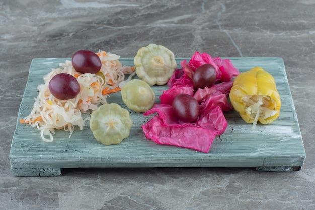 Gros plan photo de légumes en conserve sur planche de bois.