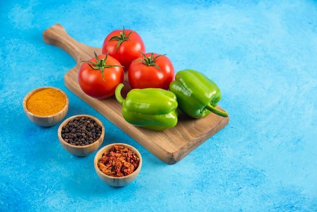 Gros plan photo de légumes sur planche de bois et épices.