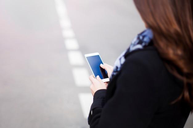 Gros plan photo de maquette de mains féminines avec un smartphone avec un écran blanc en plein air