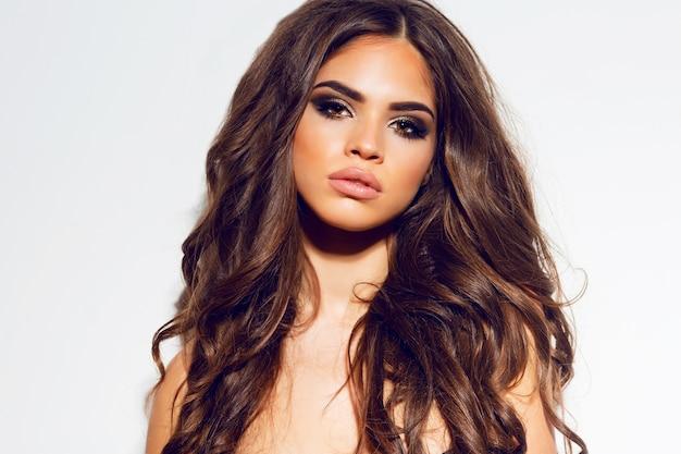 Gros plan photo de mode de jeune femme aux cheveux longs et bouclés beauté
