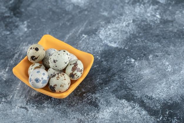 Gros plan photo d'œufs de caille bio dans un bol jaune.