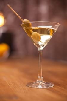 Gros plan photo d'olives vertes dans un verre de martini sec. cocktail savoureux. verre en crystal.