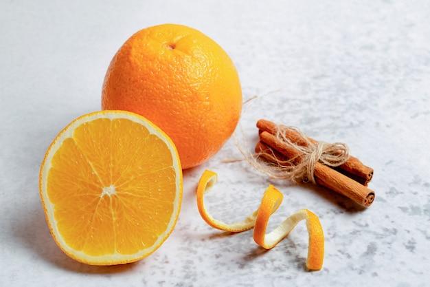 Gros plan photo d'une orange fraîche à moitié coupée ou entière avec de la cannelle.