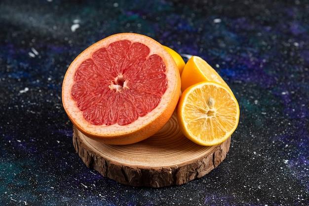 Gros plan photo pamplemousse et citron coupés à moitié sur planche de bois.