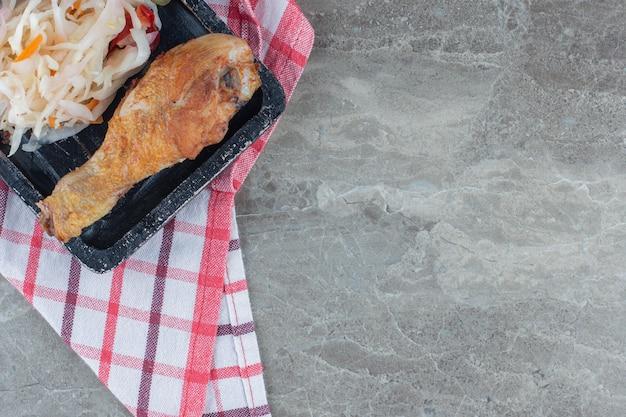 Gros plan photo.pf tas de choucroute et cuisse de poulet sur plaque de bois.