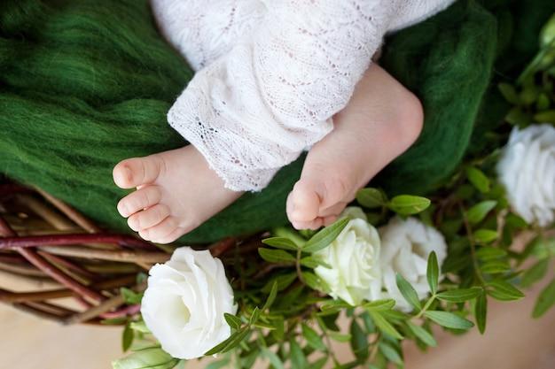 Gros plan photo de pieds de bébé nouveau-né sur des fleurs et des carreaux tricotés