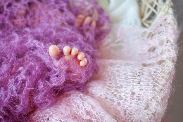 Gros plan photo de pieds de bébé nouveau-né en plaid tricoté