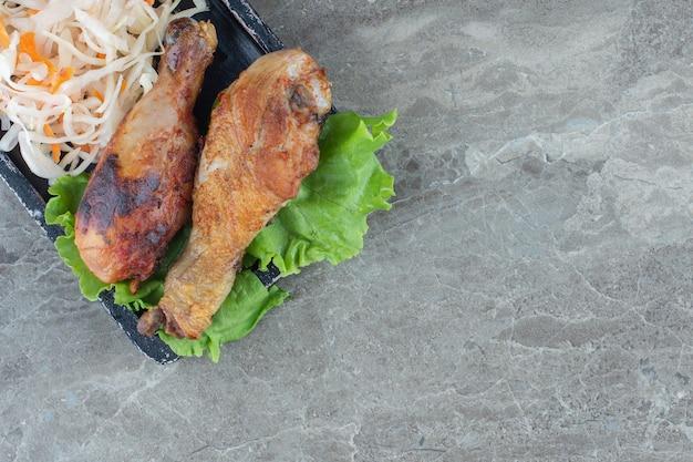 Gros plan photo de pilons de poulet grillés avec feuille de laitue et choucroute.