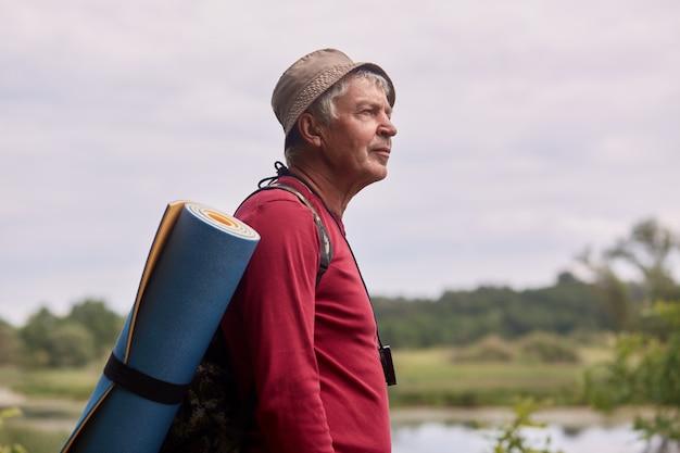 Gros plan photo de profil d'un homme âgé avec sac à dos