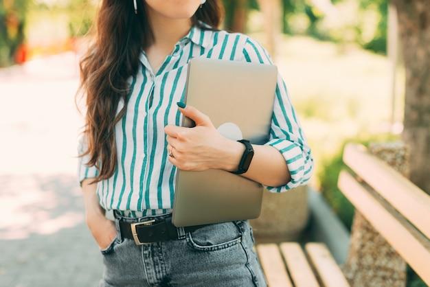 Gros plan photo recadrée d'une jeune femme décontractée tenant un ordinateur portable à l'extérieur dans le parc de la ville